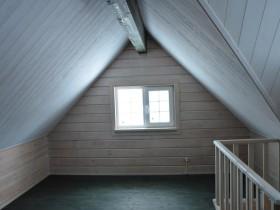 оригинальное решение мансардного этажа подчеркнуто выразительной пластикой балки конька из клееного бруса.