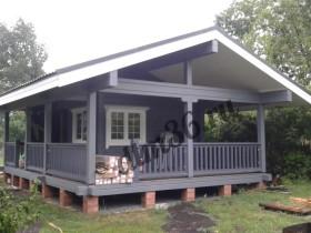 строительство деревянного дома у пруда с деревянной верандой из лиственницы.