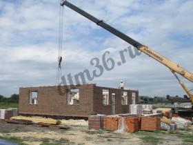 строительство дома, для подачи кирпичей используется спецтехника.