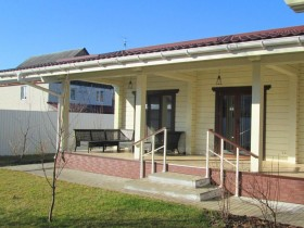 терраса деревянного дома, большие окна в пол делает помещение с большим бассейном светлым и уютным.